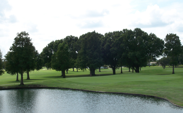 A pond is surrounded by trees at River Greens Golf Course in Avon Park, Florida